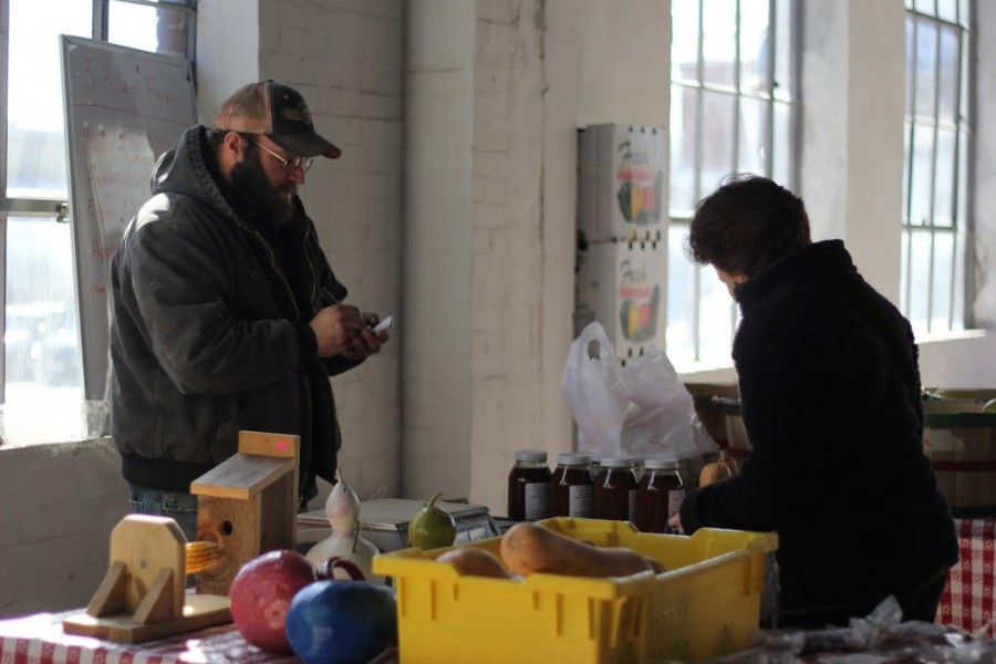 A+local+vendor+writes+down+an+order+for+a+customer+at+the+Lexington+Farmer%27s+Market+--+now+located+indoors+for+the+winter.