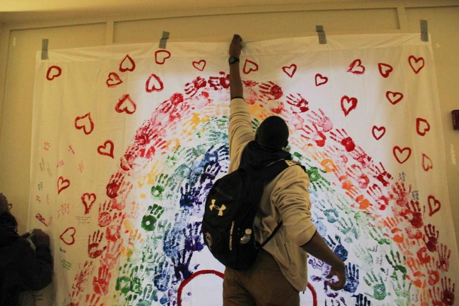 Jok Asiyo, '16, hangs the banner.