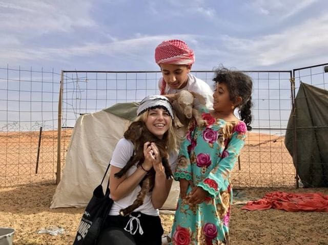 Lauren Fredericks, '20, holds a baby goat with new friends in Oman. Photo courtesy of Fredericks.