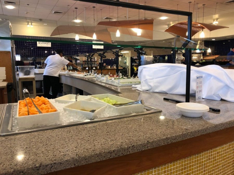 A Marketplace employee prepares the salad bar for dinner. Photo by Kaelan McCabe, '21.