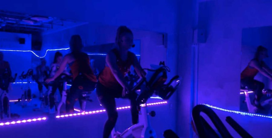 Kathryn Young, '19, teaches a spin class at fLEX Fitness, which is her way of making cardio fun. Photo by Gigi Lancaster.