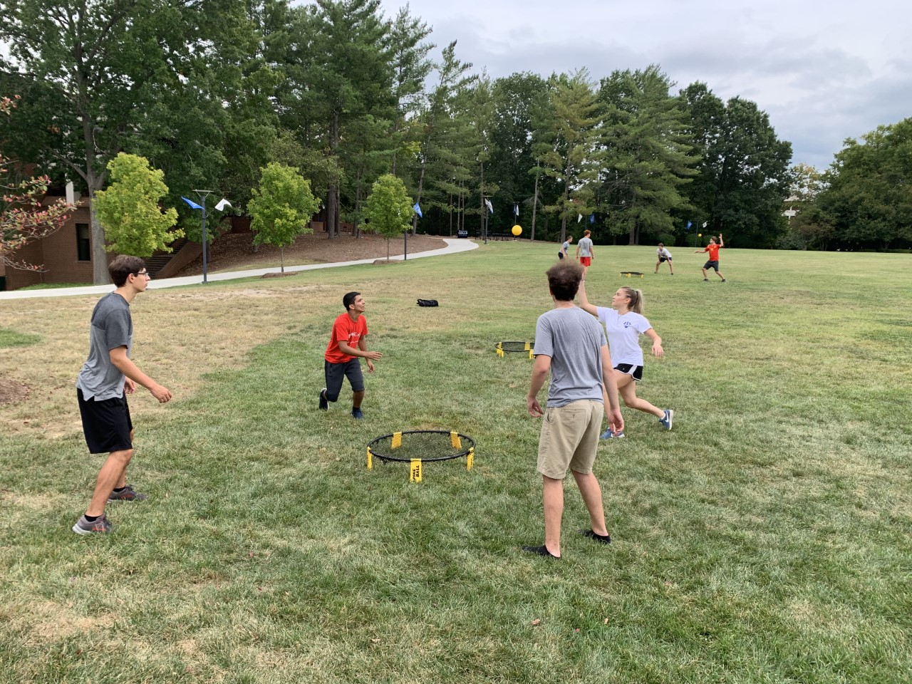 Students play Spike Ball together on a green field.