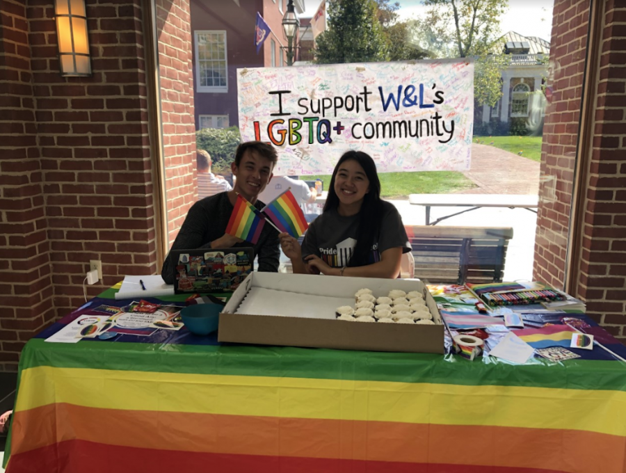 Ben Hess, '23, and Lauren Hollis, '23, hold up flags at the Pride Week table in Commons. Photo by Grace Mamon.