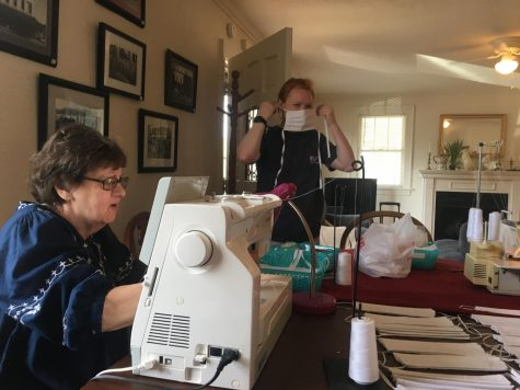 Linda Floyd (left) sews the two pieces of cloth together to make the base of the mask. Mary Katherine Lawrence (right) tests out the sizing on her face.  Photo by Hannah Denham.