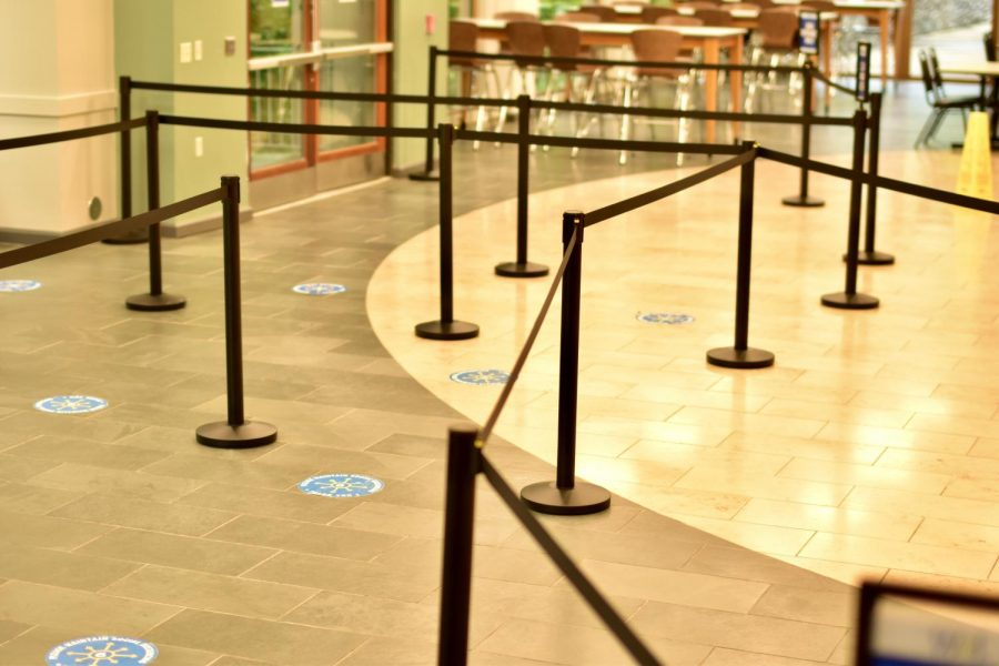Ropes and signs facilitate social distancing while students wait in line.